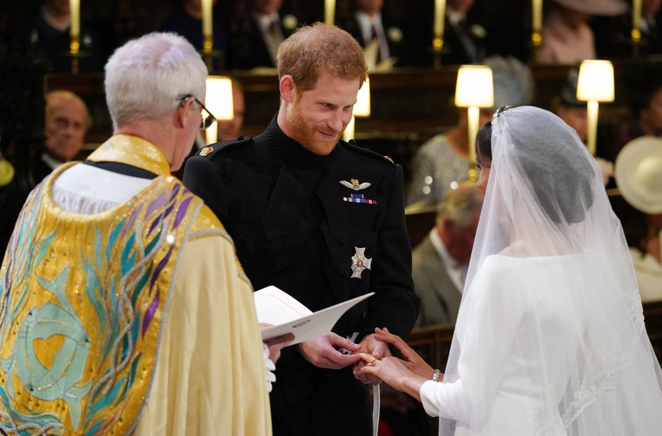 Prince Harry places the wedding ring on the finger